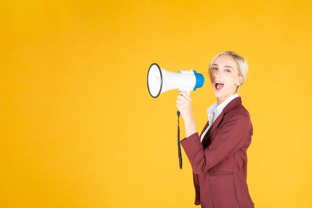 ビジネスの女性は、黄色の背景にメガホンから発表しています