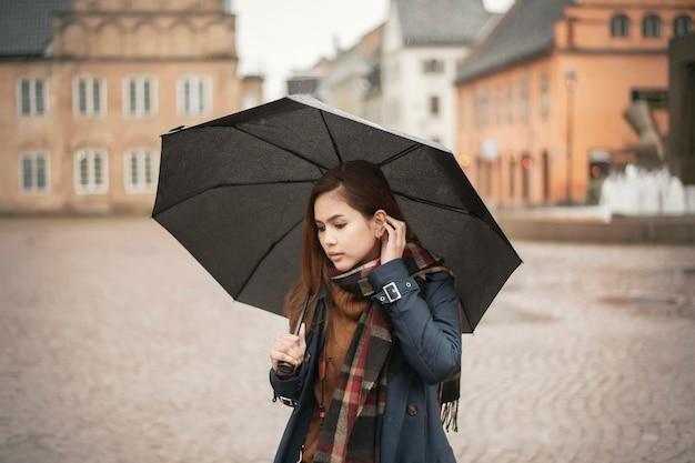 雨の日に美しい女性が傘を差している