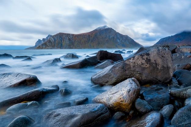 日没のロフォーテン諸島の壮大な山と美しい青い海