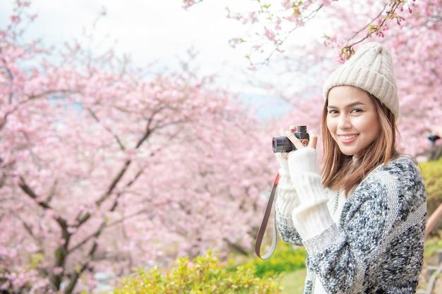 魅力的な女性は日本の松田で桜と楽しんでいます。