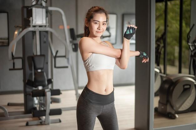 美しいアジアの女性は、ジムで運動をしています。