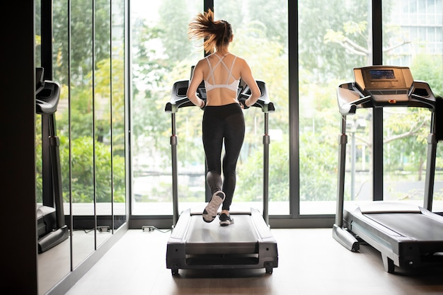 Красивая азиатская женщина спорта бежит на беговой дорожке в спортзале