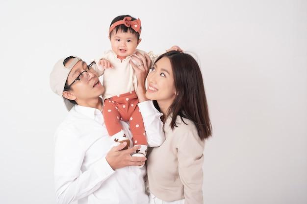 Счастливая азиатская семья на белой стене