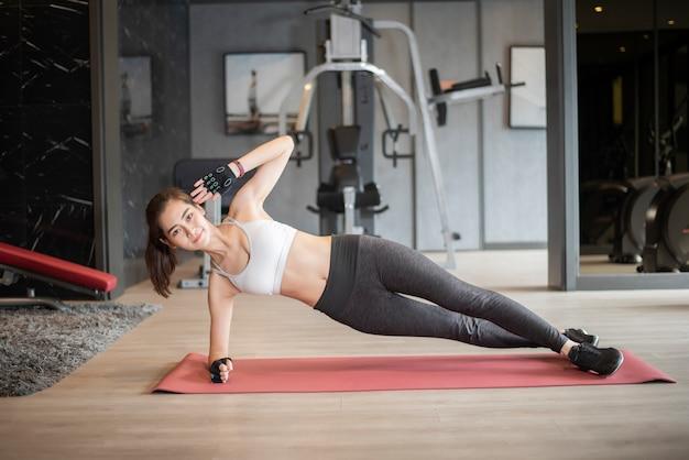 美しいアジアの女性はジムで運動をしています。