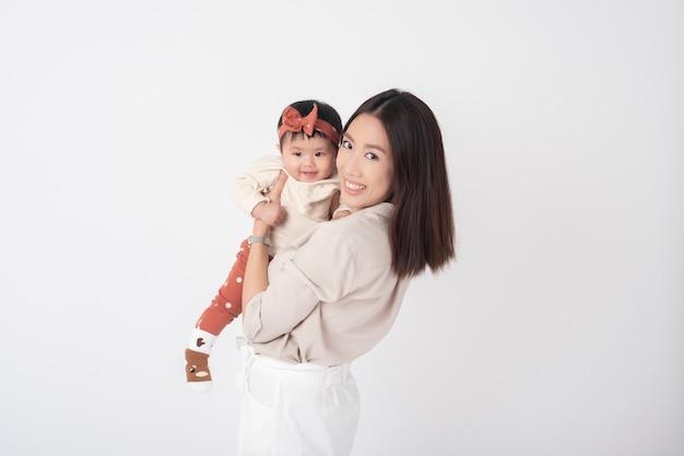 Азиатская мать и очаровательная девочка счастливы на белой стене