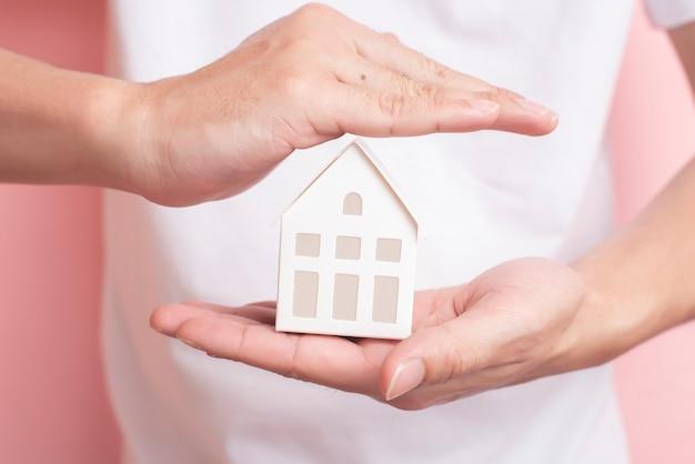 Маленький белый дом на человеческой руке