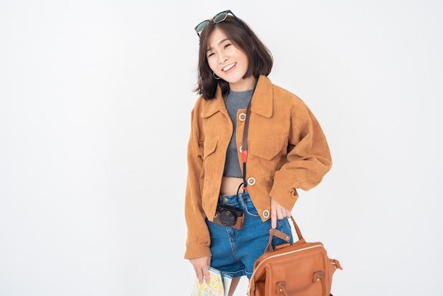 白い壁に幸せな美しい若いアジア観光女性
