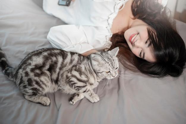 Красивая азиатская женщина любовника кота играет с котом в ее комнате