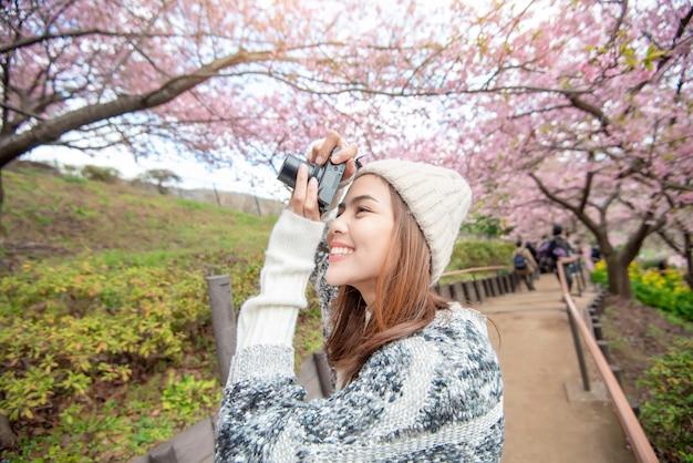 魅力的な女性は公園で桜と楽しんでいます。
