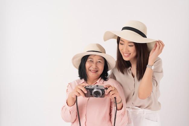 アジアの年上の女性と彼女の娘の白い壁に