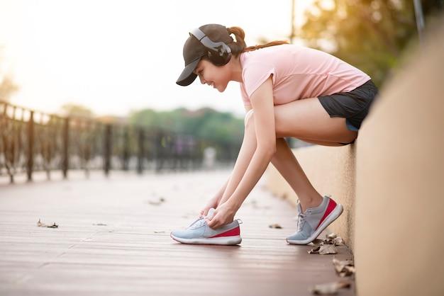美しい女性は音楽を聴いていると公園で靴を結ぶ