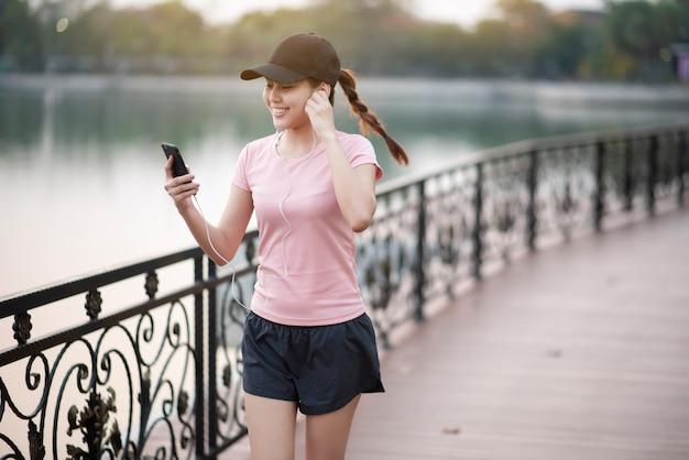 美しい女性は音楽を聴くと公園でジョギング