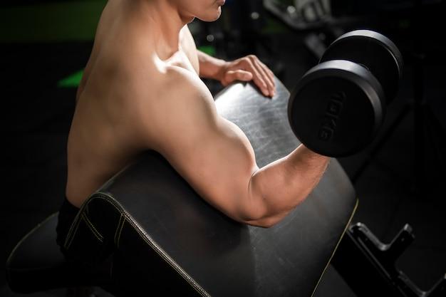 筋肉フィットネス男性ボディービルダーはジムでダンベルでトレーニング