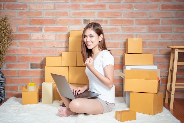 女性起業家のオーナーである中小企業のビジネスは、電話、ラップトップ、梱包箱で注文を確認して顧客に送ります