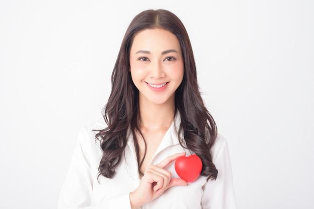 美しいアジアの女性は赤いハート(ヘルスケアの概念)を保持しています。