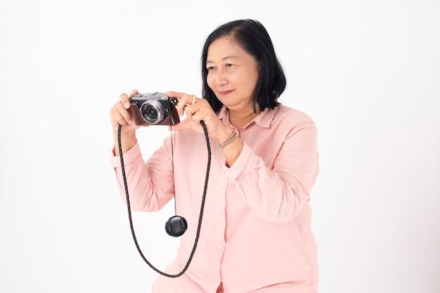 写真のカメラを持つアジアの年上の女性