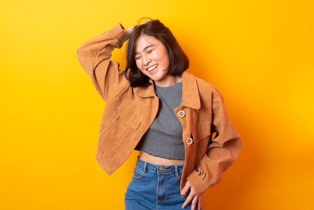 黄色の壁に満足して美しいアジアの女性大学生