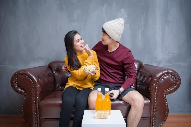 Счастливая пара сидит дома и смотрит фильмы