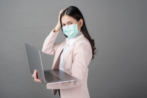 サージカルマスクを持つ女性実業家がラップトップコンピューターを保持しています。