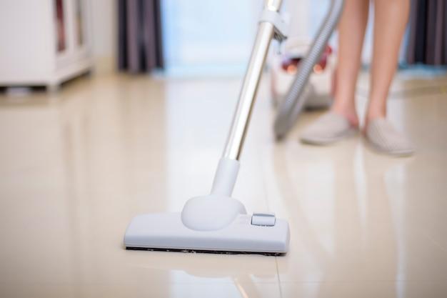 女性は掃除機で家の掃除