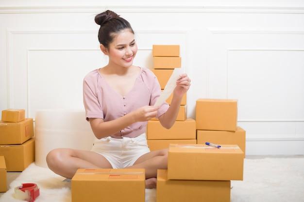 Женщина готовит продукты с картонными коробками к отправке.