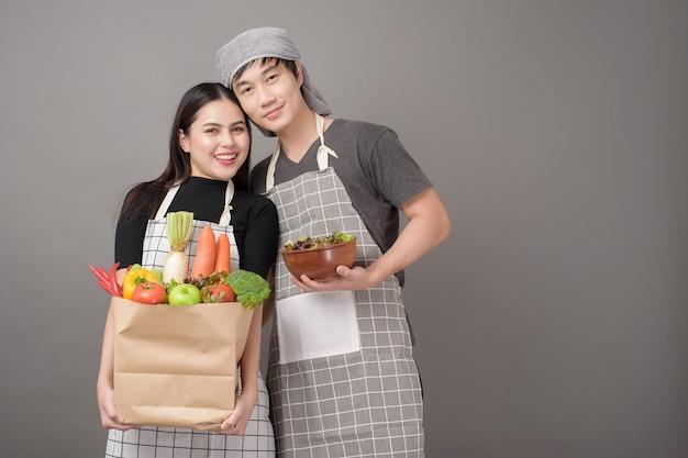 Счастливая пара держит овощи в продуктовой сумке серая стена