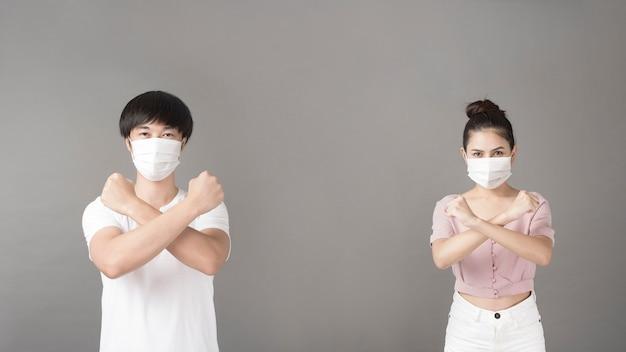 Портрет мужчины и женщины с хирургической маской в студии, концепция социального дистанцирования