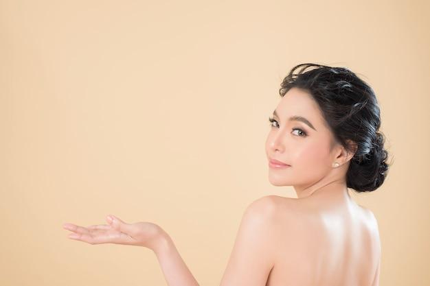 美しい完璧な肌のスタジオでゴージャスな若い女性の肖像画