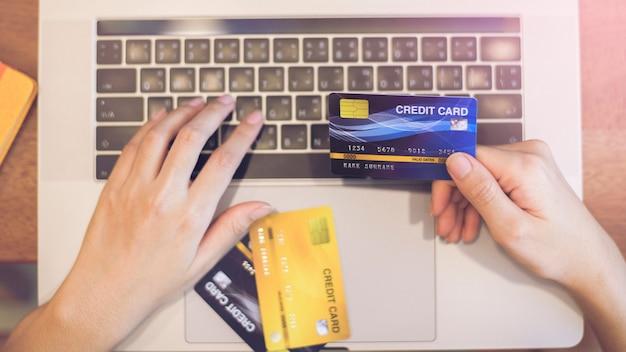女性の手がクレジットカードを持っている、オンラインショッピング