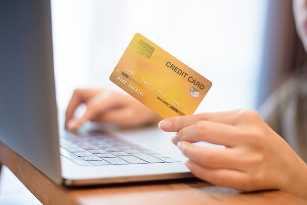 女性の手はクレジットカードを持っています。