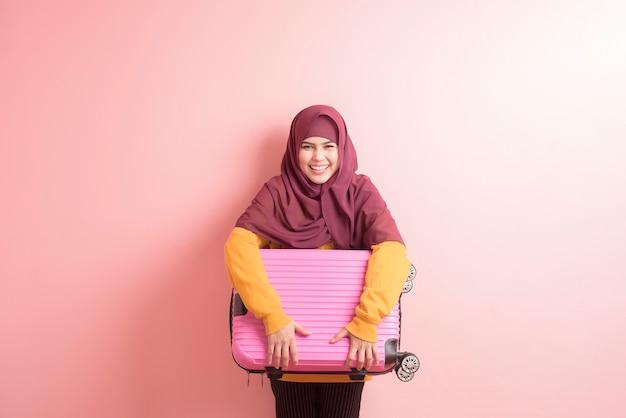 ヒジャーブとイスラム教徒の女性がピンクの背景に荷物を持っている、人々旅行の概念