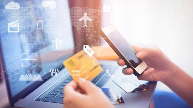 女性の手はデジタル仮想画面上のオンラインショッピングアイコンでクレジットカードを持っています。