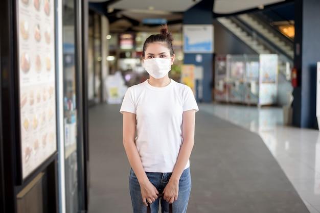 屋外に立っているマスクを持つ若い女