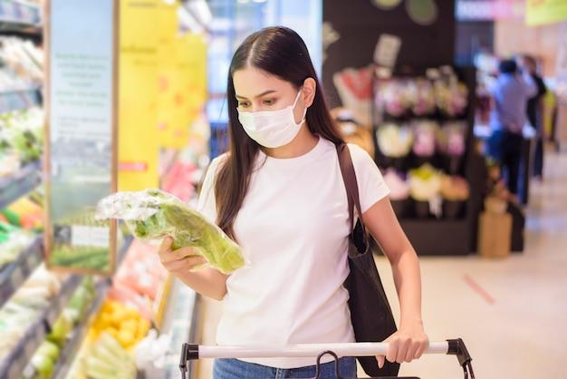 女性はフェイスマスクとスーパーで買い物