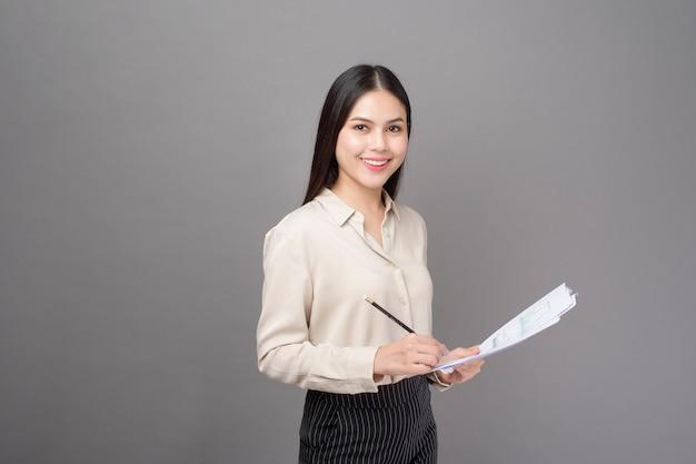 Молодая бизнес-леди анализирует бизнес-план на сером фоне