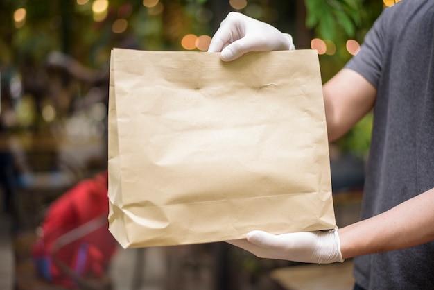 Азиатский доставщик носит лицевую маску, держит продуктовый мешок, концепцию безопасной доставки на дом