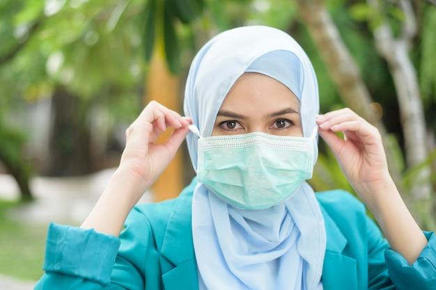 ヒジャーブとイスラム教徒の女性は屋外でフェイスマスクを着ています。
