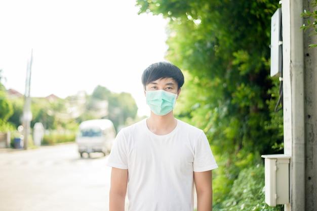 Молодой азиатский человек носит маску в городе на открытом воздухе