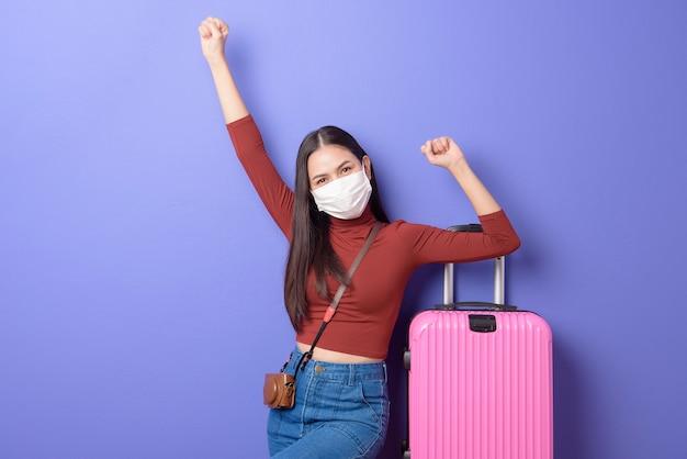 フェイスマスク、新しい通常の旅行の概念を持つ若い旅行者の女性の肖像画
