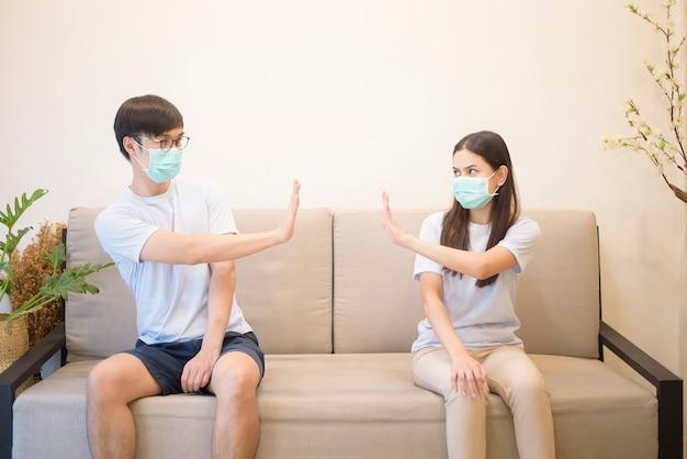 保護のためとコロナウイルスを避けるために、マスクをしているカップルが隔離中に自宅のソファーに座っています。