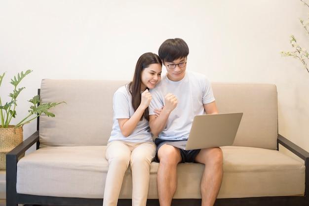 Молодая счастливая пара отдыхает и использует ноутбук на диване у себя дома