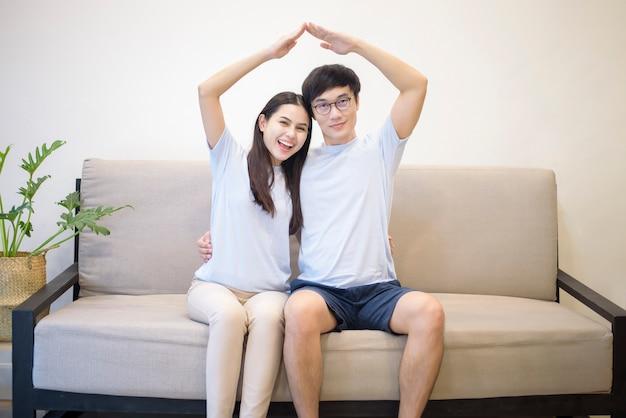 Пара в синей рубашке сидит на диване и делает крышу дома