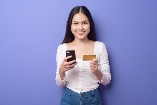 Портрет молодой азиатской женщины использует мобильный телефон с кредитной карты на фиолетовом фоне