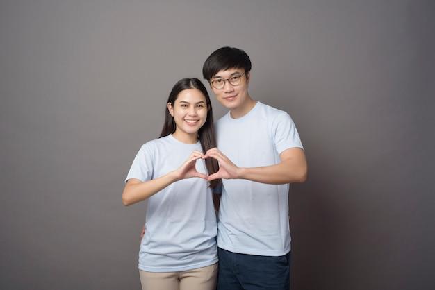 Портрет счастливой пары в синей рубашке делает сердечко руками над серым