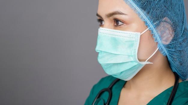 緑のスクラブで自信を持って若い女性医師は灰色の上のサージカルマスクを着ています。