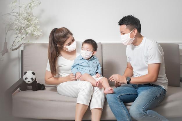 幸せなアジアの家族はフェイスマスクを着て家にいます。
