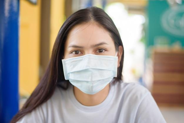 若い女性がタイのストリートフードを食べて、フェイスマスクを身に着けている、新しい通常の食事のコンセプト