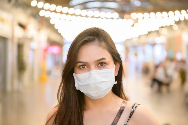 若いアジアの女性はショッピングセンター、コロナウイルス保護、新しい通常のライフスタイルコンセプトでショッピング防護マスクを着ています。