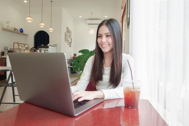 若い女性はコーヒーショップで彼女のラップトップで働いています。