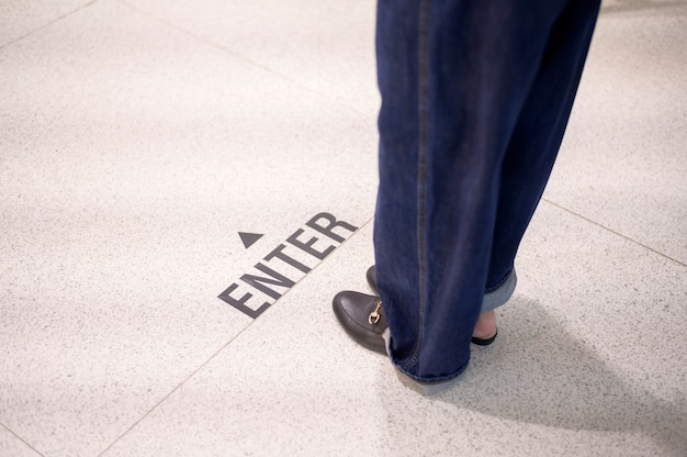 ショッピングモールの社会的距離の線に立っている女性の足を閉じる